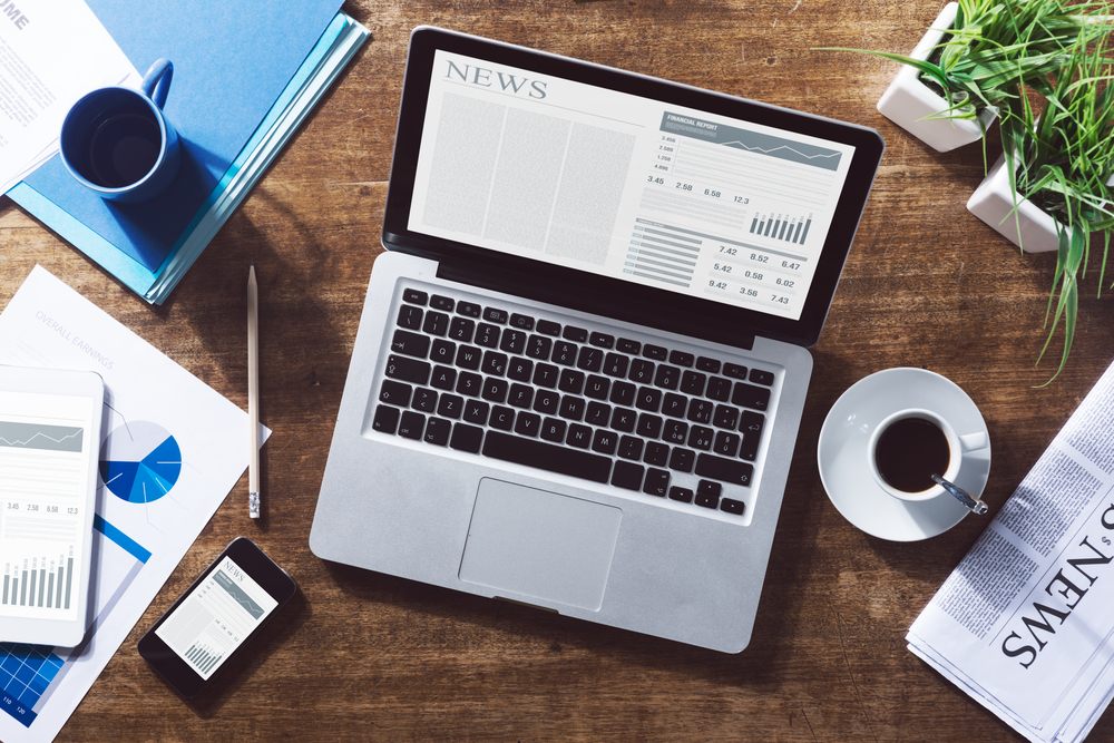 Financial business news online on a laptop with coffee and stationery